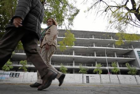 Dos viandantes pasean justo por delante de la estructura del edificio a medio hacer de la avenida Ramón y Cajal. / Pepo Herrera
