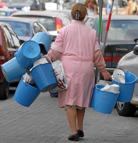 Una trabajadora sevillana de la limpieza cargada de cubos de la fregona.