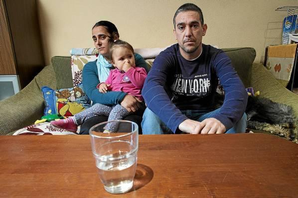 Vanesa Pérez y Abel Hernández, junto a una de sus hijas, Mara, en el salón de su casa frente a un vaso de agua