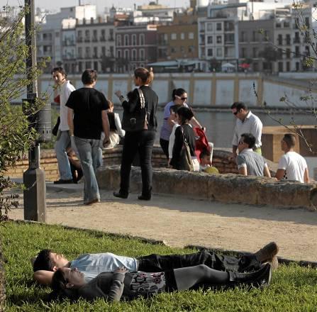 Jóvenes disfrutan junto al río del buen tiempo con el que ayer entró la primavera en la ciudad.