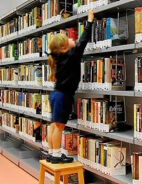Una niña intenta alcanzar uno de los 40000 volúmenes disponibles.