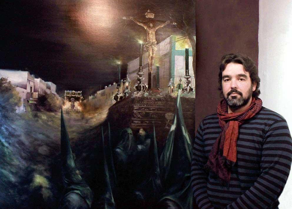 El artista Miguel Ángel González posa en su estudio ante la pintura que anuncia la Semana Santa de Castilblanco de los Arroyos. / J.C.R.