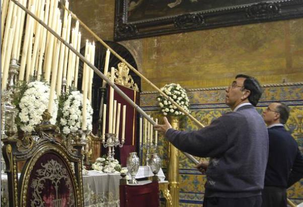 Manuel Santizo García, tercera generación de la saga, dando lumbre con una caña al altar de cultos de laSoledad de San Lorenzo en una foto del álbum familiar. / El Correo