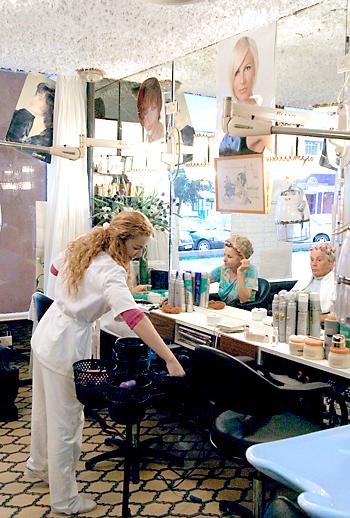 Una peluquera atienda a una cliente en una peluquería de Málaga. / Álex Zea
