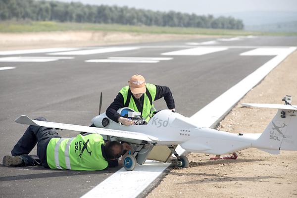 Dos técnicos trabajan en un prototipo sobre la pista de vuelo en el centro de vuelos experimentales ATLAS. / EFE
