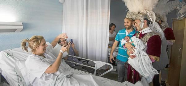 Un armao sostiene a un recién nacido en el Hospital de la Mujer mientras sus padres inmortalizan el momento con los móviles. / Carlos Hernández