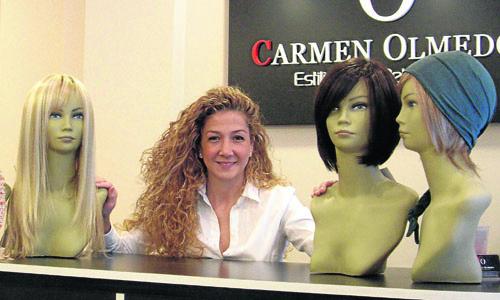 Carmen Olmedo entre algunos modelos de pelucas de su salón de belleza.