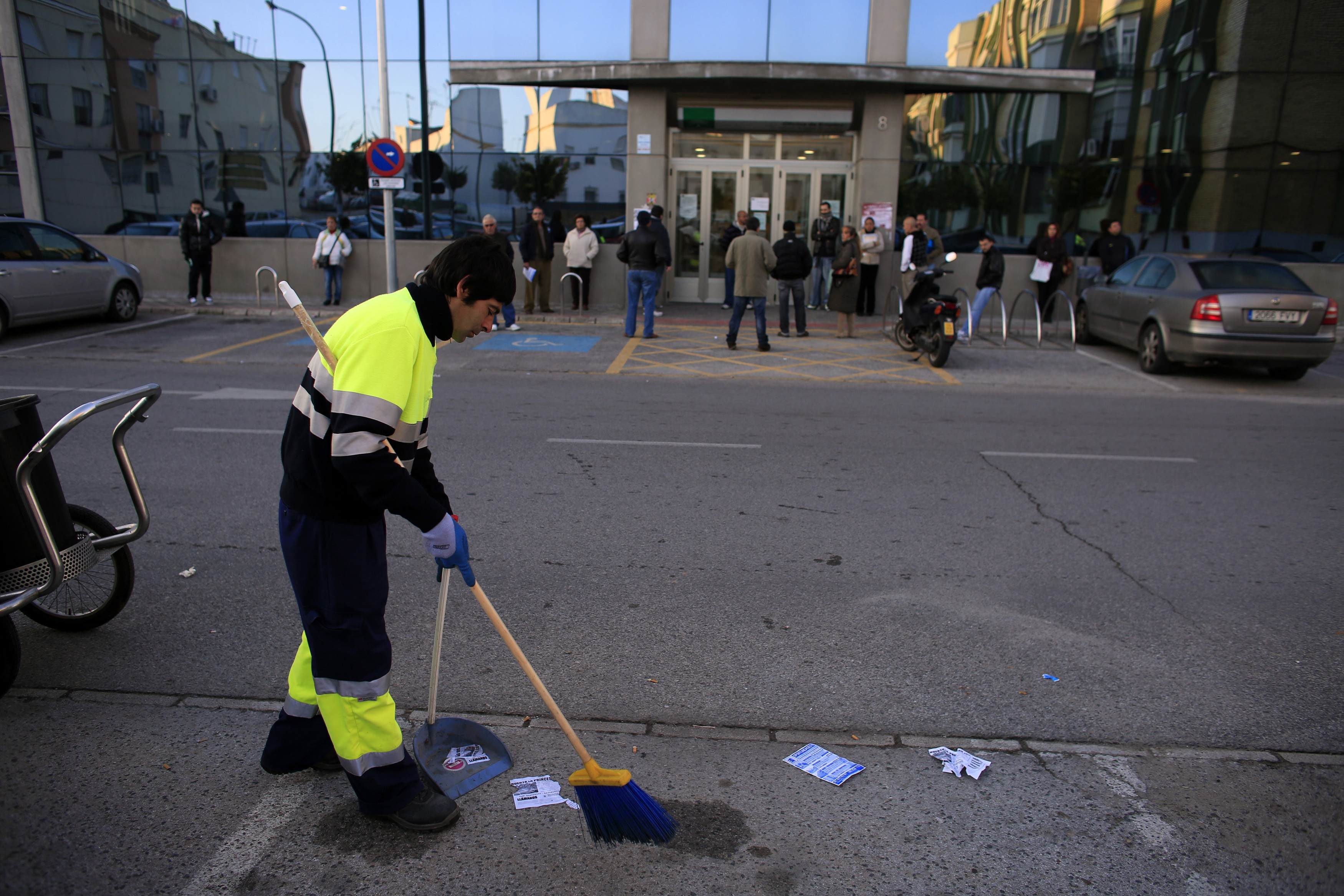 People wait to enter in a government-run employment office as a street cleaner sweeps on a street in Dos Hermanas