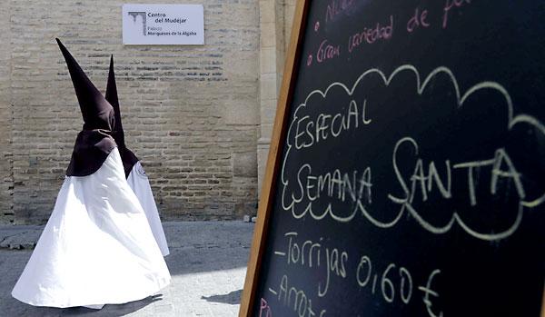 Nazarenos del Carmen Doloroso discurren ante la pizarra de un establecimiento de hostelería que oferta torrijas a 60 céntimos. / José Luis Montero