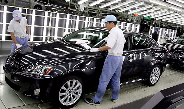 Operarios trabajan en una cadena de montaje de automóviles. / EFE