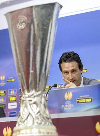 El entrenador del Sevilla, Unai Emery, señala la antigua Copa de la UEFA que se entregará al campeón de la Liga Europa, durante su comparecencia previa al partido Sevilla-Valencia. / EFE