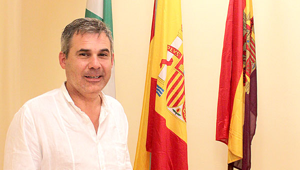El alcalde de Villaverde del Río, Santiago Jiménez,  en el salón de actos del Ayuntamiento que preside de bandera de España flanqueada de la andaluza y la tricolor. / J.C.Romero