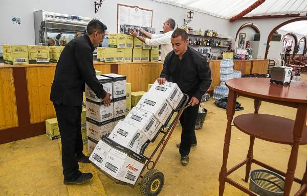 El aprovisionamiento de botellas de manzanilla en el interior de las casetas tiene lugar antes de la llegada de los primeros feriantes. / fotos: Carlos Hernández