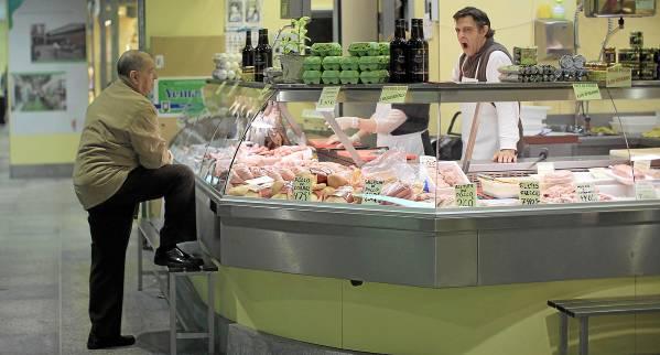 Un jubilado realiza su compra en un puesto de la céntrica plaza de abastos de la Encarnación, en Sevilla capital / MARCELO DEL POZO (REUTERS)