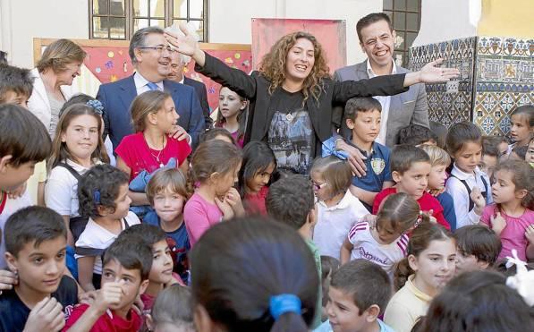 Estrella Morente, entre el alcalde, Juan Ignacio Zoido y el director de la Bienal, Cristóbal Ortega, rodeada de los alumnos del CEIP San Jacinto. / Pepo Herrera