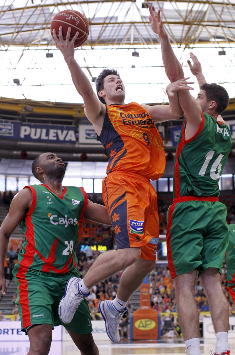El base belga del Valencia Basket Club, Sam Van Rossom (c), entre los aleros del Cajaso, el italiano Marcos Mata (d) y el norteamericano Marcus Landry, durante el partido correspondiente a la 32 jornada de Liga Endesa disputado hoy en Valencia.