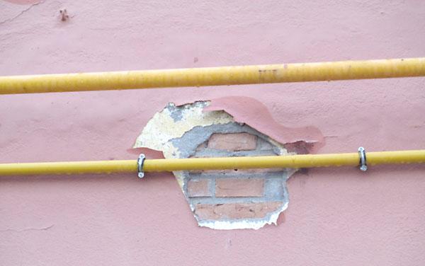 Un desconchón en la fachada deja a la vista algunos de los ladrillos.
