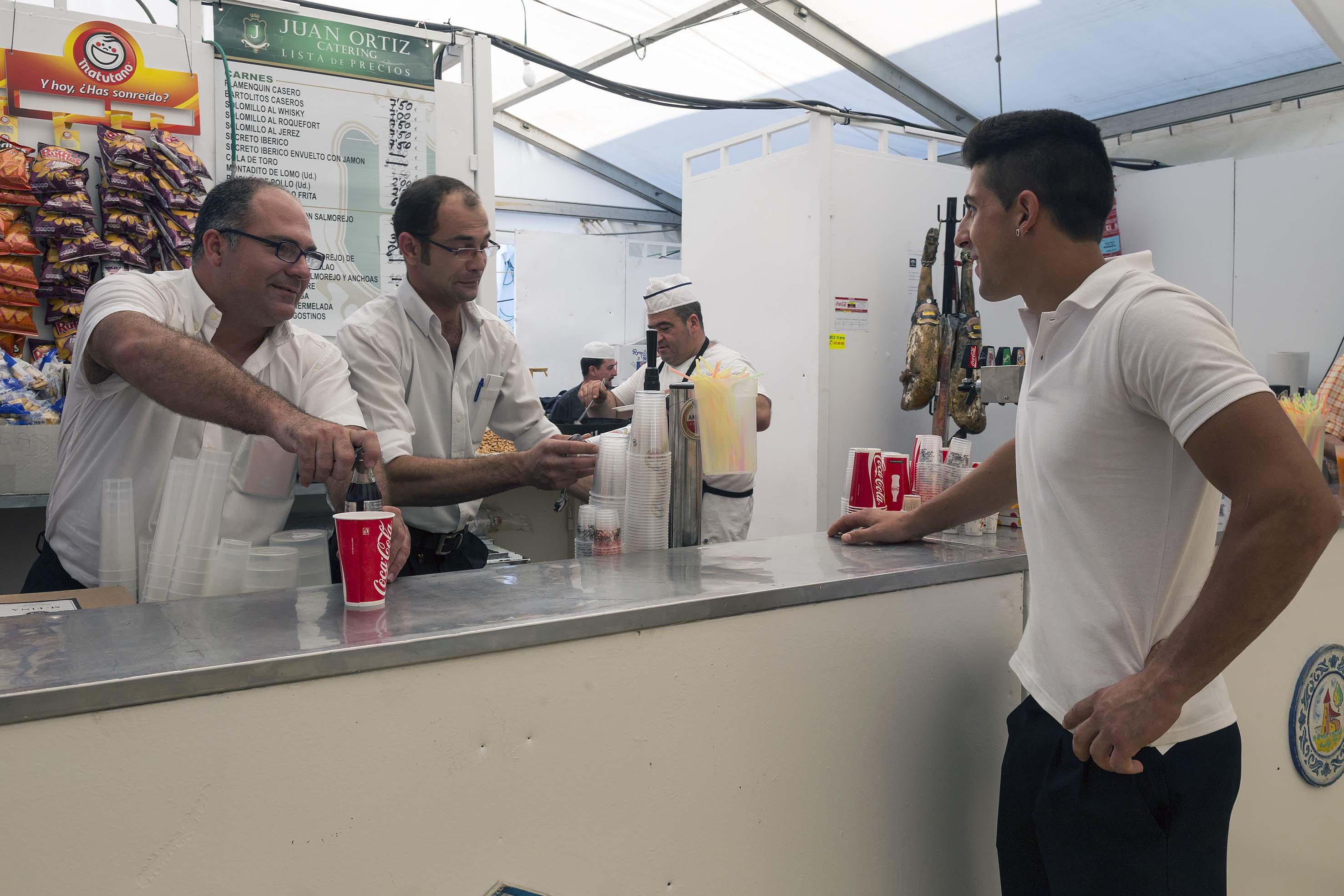 Dos camareros sirven bebidas en una de las casetas. / José Luis Montero