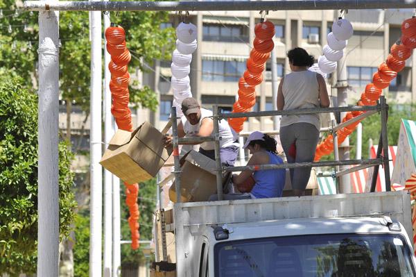 Colocación de los últimos farolillos en las calles con los nombres de toreros, ayer martes, desde lo alto de una camioneta. / J.M. Paisano