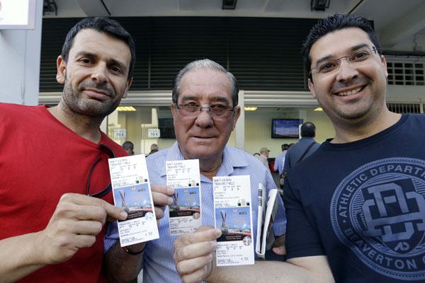 Tres sevillistas muestran con orgullo su entrada para la final. / Jose Luis Montero