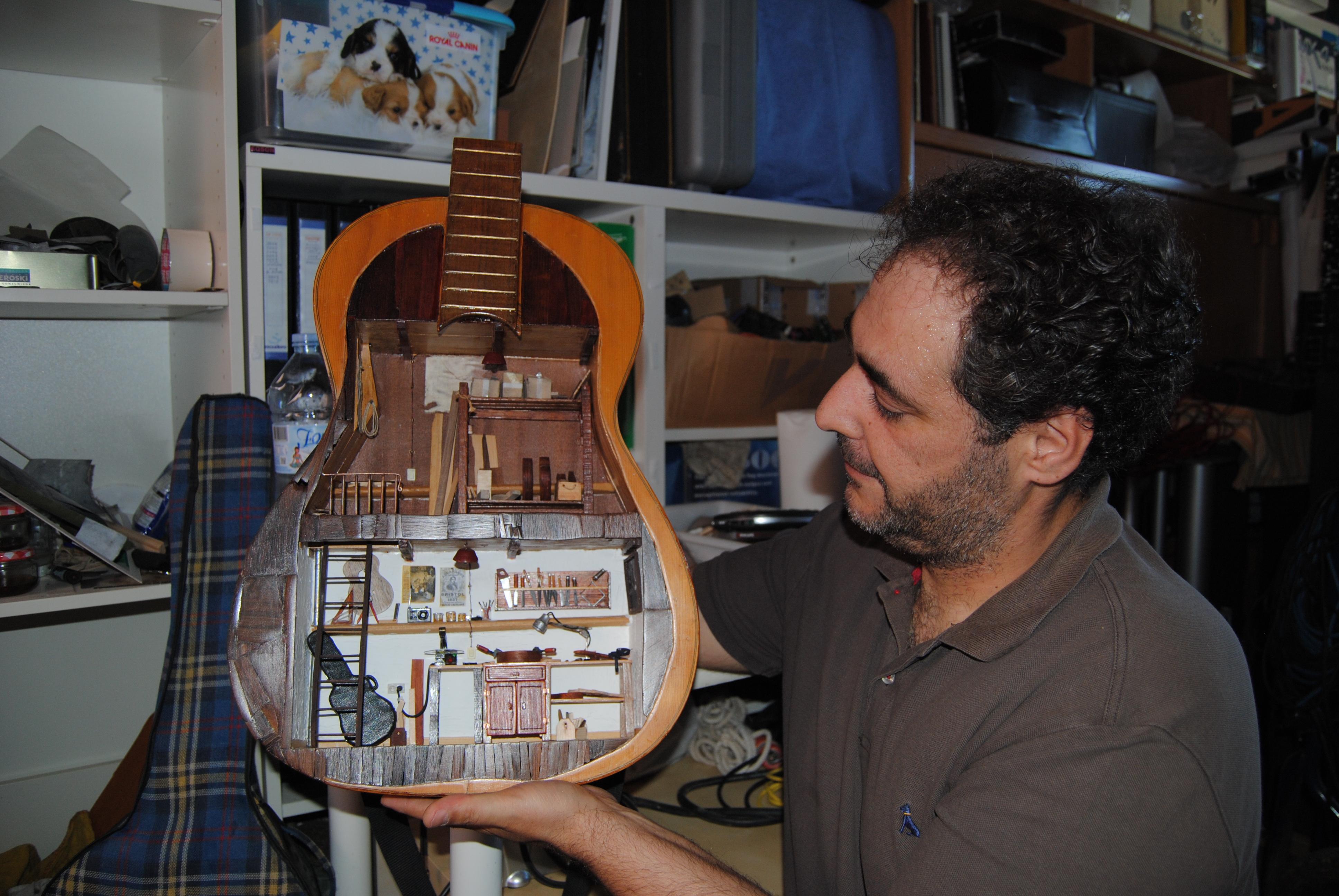 El artista moronense, con su taller de guitarras en miniatura dentro de una guitarra española. Foto: María Montiel