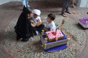 Una niña de mantilla anima a dos de los pequeños costaleros de Utrera. FOTO: Salvador Criado