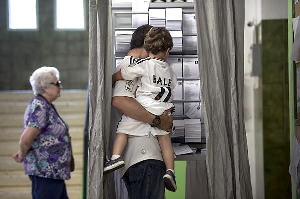 CÓRDOBA. Un padre con su hijo vestidos con la camiseta del Real Madrid, en un colegio electoral de Córdoba durante la jornada de las elecciones al Parlamento Europeo. EFE/Rafa Alcaide
