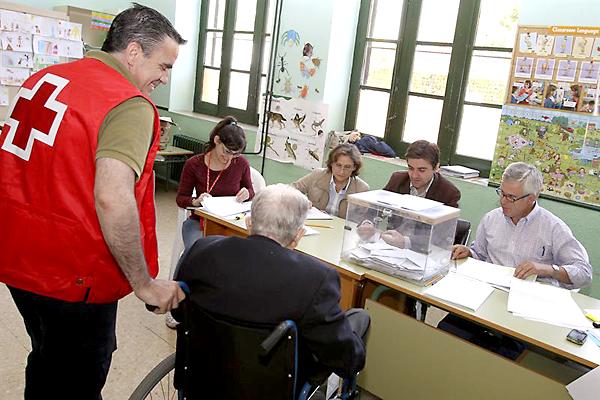CIUDAD REAL. Voluntarios de la Cruz Roja trasladan a un anciano hasta colegio Carlos Eraña de Ciudad Real, para que ejercite su derecho al voto en la jornada de elecciones al Parlamento Europeo. / EFE.Mariano Cieza