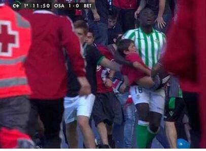 N'Diaye lleva en brazos a un niño herido en la caída desde la grada.