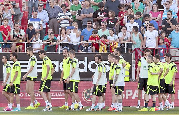 Los jugadores de la selección española de fútbol pasan junto a numerosos aficionados en el entrenamiento realizado esta tarde en el estadio Ramón Sánchez Pizjuán. / Julio Muñoz (EFE)