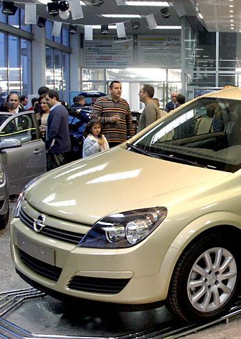 Un grupo de clientes prueban distintos modelos de coches en el concesionario sevillano Suauto.
