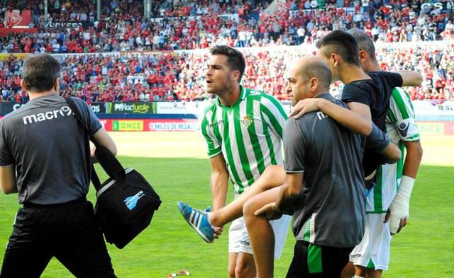 Chica, Salva Sevilla y José Manuel Acuña, con la ayuda de José María Montiel, llevan a otro de los heridos / EFE