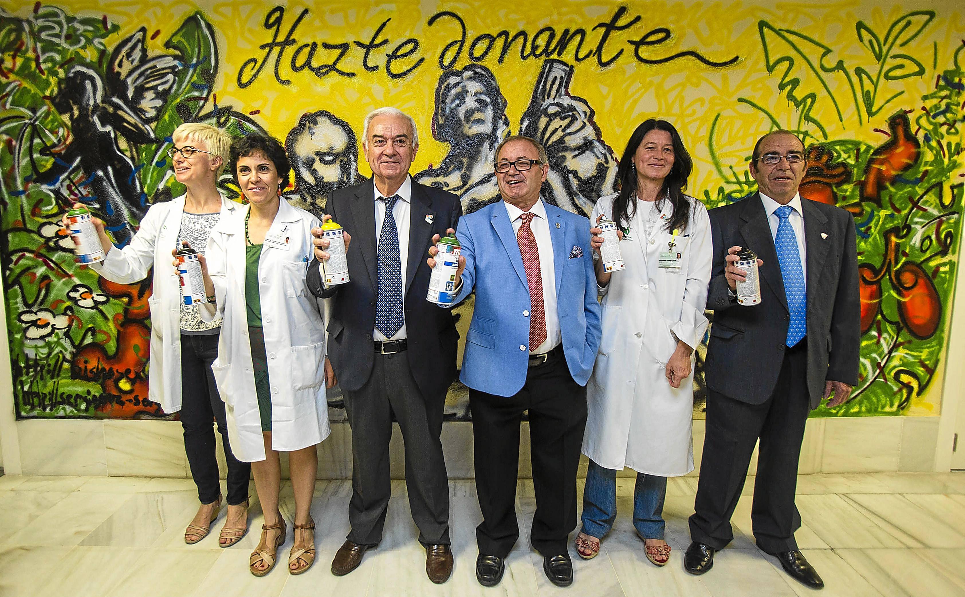 Facultativos del equipo de trasplantes y responsables de las asociaciones de pacientes completaron ayer un grafiti de Sergio Cruz y Bisho en homanaje a los donantes en el hospital Virgen del Rocío. / Carlos Hernández