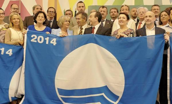 El consejero de Turismo y Comercio, Rafael Rodríguez, posa con una bandera azul y con los regidores de las playas andaluzas que han obtenido este distintivo.