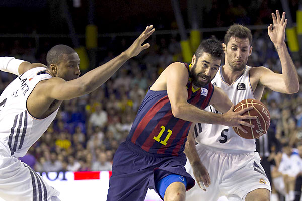 El escolta del FC Barcelona, Juan Carlos Navarro (c), intenta superar la defensa del alero del Real Madrid, Rudi Fernández (d), y el pívot estadounidense Marcus Slaughter (i), durante el partido. / EFE