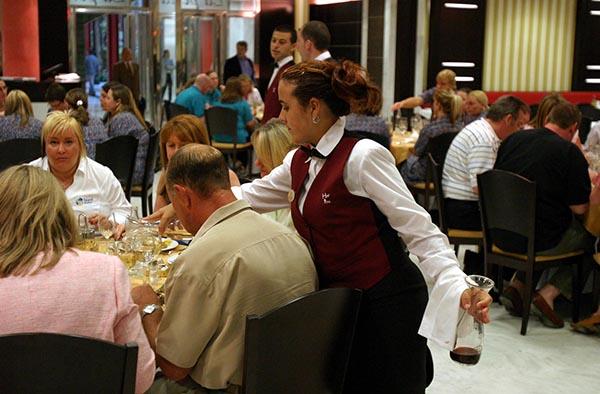 Una camarera atiende una mesa en un complejo turístico de Málaga. / Álex Zea