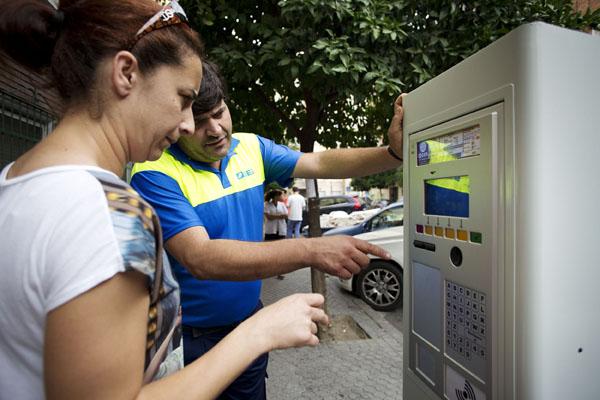 Un trabajador de AUSSA le explica a una usuario cómo funciona el parquímetro en la zona de Bami. / Pepo Herrera