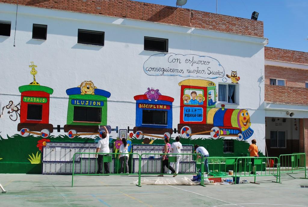 Un grupo de voluntarios termina de pintar la pared en la que reza la frase «Con esfuerzo conseguimos nuestros sueños». Foto: Salvador Criado