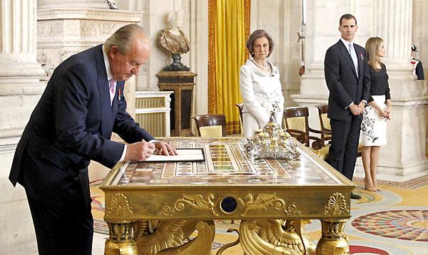 El Rey Juan Carlos, en presencia de la Reina Sofía y los Príncipes de Asturias, firma esta tarde la ley orgánica que hará efectiva a medianoche su abdicación. / EFE