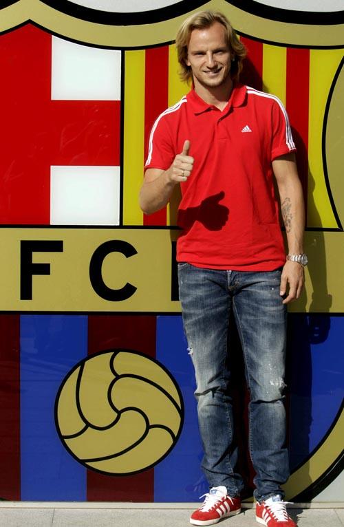 El centrocampista croata Ivan Rakitic posa esta tarde junto al escudo que preside la entrada de las oficinas del FC Barcelona. / EFE