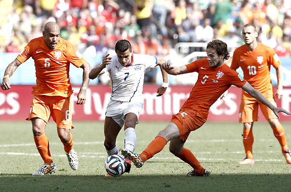 El delantero chileno Alexis Sánchez (c) avanza con el balón ante el centrocampista holandés Nigel de Jong (i) y su compañero el defensa Daley Blind. / EFE