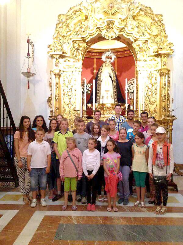 Los niños acogidos por la hermandad del Cachorro, pionera de este programa. Detrás, la imagen de la Virgen del Patrocinio.