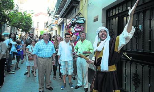 Uno de los actores muestra a los sevillanos y turistas algunos de los enclaves históricos de la ciudad. /J.M. Paisano