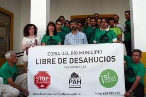 El alcalde de Coria del Río junto a miembros de la PAH con la banderola.