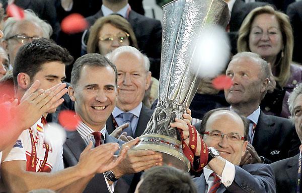 El príncipe Felipe y el presidente del Sevilla, José Castro, levantan el trofeo tras ganar el Sevilla FCla Europa League en Turín. / EFE