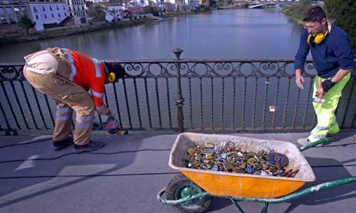 Trabajadores del ayuntamiento de Sevilla retiran los últimos candados puestos en las rejas del puente de Isabel II, conocido como el puente de Triana.