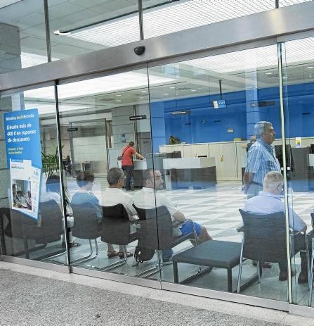 Clientes esperando su turno en una sucursal bancaria del centro de la capital sevillana. / J.M.PAISANO