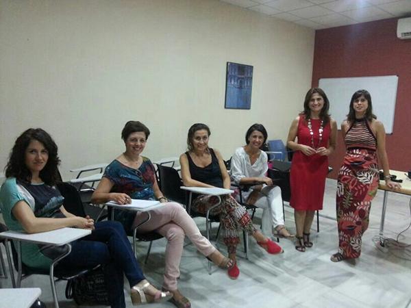 Las psicólogas María del Mar Tirado y Marta Díez, de pie, junto a algunas de las madres asistentes al taller.