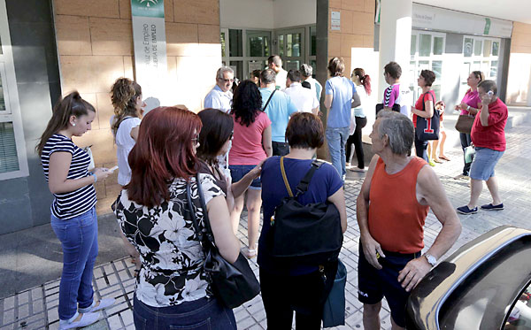Desempleados esperando a que abra una de las oficinas del SAE en la capital hispalense, en concreto en Sevilla Este. / José Luis Montero