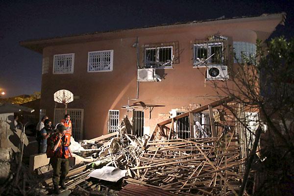 Varios oficiales de seguridad israelíes inspeccionan los daños de una casa tras haber impactado sobre ella directamente un misil desde la Franja de Gaza. / EFE